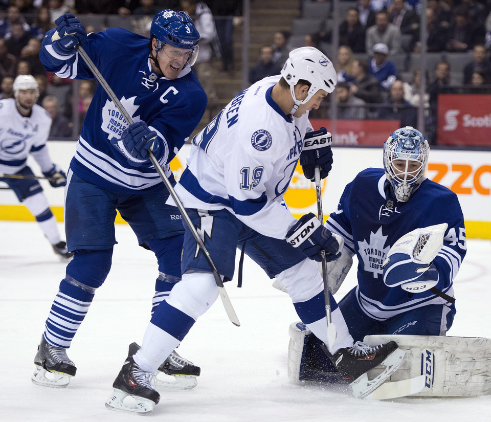 Photo - Toronto Maple Leafs goaltender Jonathan Bernier, right, puts his glove up to make a save as Dion Phaneuf (3) holds off Tampa Bay Lightning right winger B.J. Crombeen (19) during first period of an NHL game in Toronto, Tuesday, Jan. 28, 2014. (AP Photo/The Canadian Press, Frank Gunn)