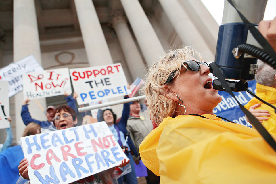 Photo - Susan McCann uses a megaphone Sunday as she helps lead a rally in support of health care reform on the south side of the state Capitol in Oklahoma City.