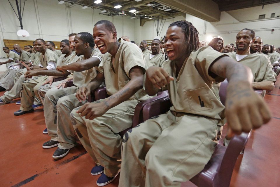 Photo - In this Aug. 27, 2013, photo, inmates, from left, Eric McNeil, Kevin Fields, and Julian Campbell, dance in their seats while watching rappers perform a hip hop adaptation of William Shakespeare's Othello, titled
