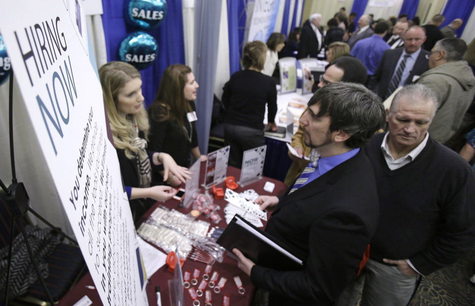 In this Wednesday, Jan. 16, 2013, photo, perspective job seekers talk with employers during a job fair in Cuyahoga Falls, Ohio. The number of Americans seeking unemployment aid jumped last week, though the increase mostly reflected difficulties the government has seasonally adjusting its numbers. Applications are still at levels signaling modest hiring.  (AP Photo/Tony Dejak)