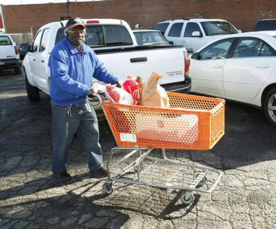 Owens Gaddis takes a shopping basket of food to his car during a Thanksgiving dinner giveaway for seniors at the Salvation Army Social Services office in Oklahoma City. <strong>PAUL HELLSTERN - THE OKLAHOMAN</strong>