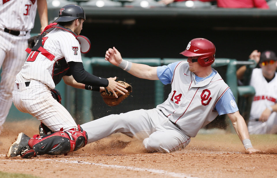 OU\'s Matt Oberste (14) slides home to score past Texas Tech catcher Mason Randolph (18) in the 8th inning during an NCAA baseball game between Oklahoma and Texas Tech in the Big 12 Baseball Championship tournament at the Chickasaw Bricktown Ballpark in Oklahoma City, Friday, May 24, 2013. OU won 8-0. Photo by Nate Billings, The Oklahoman