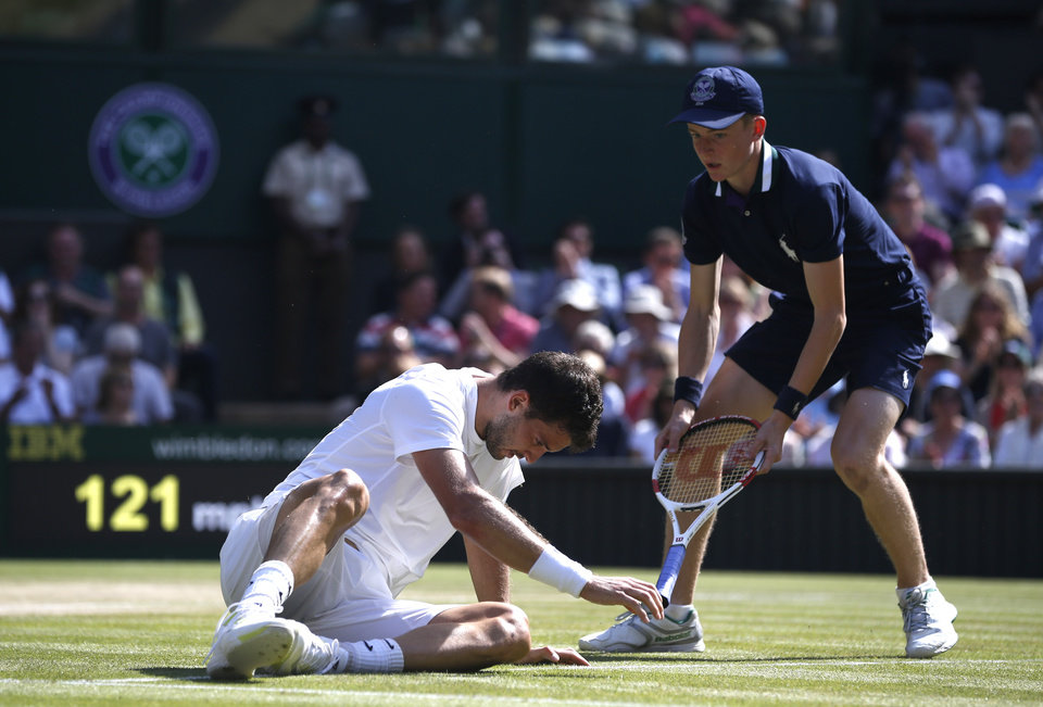 Photo - Grigor Dimitrov of Bulgaria has his racquet handed to him by a ball boy after he fell as he played against Novak Djokovic of Serbia during their men's singles semifinal match at the All England Lawn Tennis Championships in Wimbledon, London, Friday, July 4, 2014. (AP Photo/Pavel Golovkin)