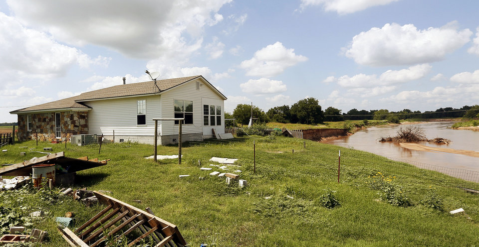 Photo - The main house on Gary and Rhonda Buford's property at 3800 N Triple X Road stands alone after the smaller house fell into the North Canadian River in Choctaw. Photo by Nate Billings, The Oklahoman  NATE BILLINGS - NATE BILLINGS