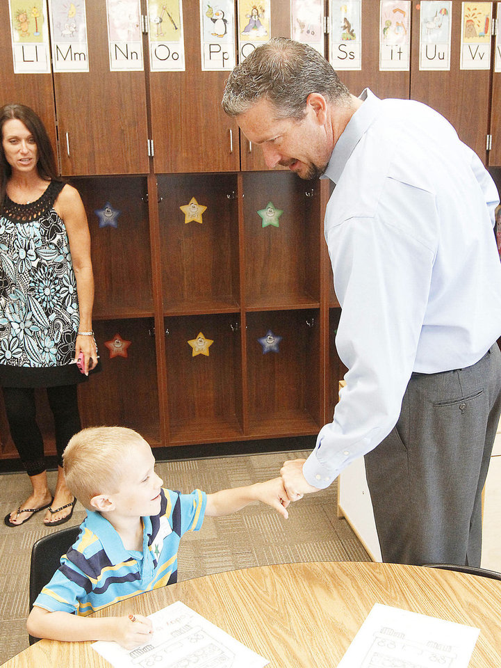 Photo - Hunter Mann, 5,  gives a hand bump to his dad, Mark Meadors, as classes for the new school year begin at Frontier Elementary School in the Edmond, OK,  school district,  Tuesday, August 20, 2013,  Photo by Paul Hellstern, The Oklahoman