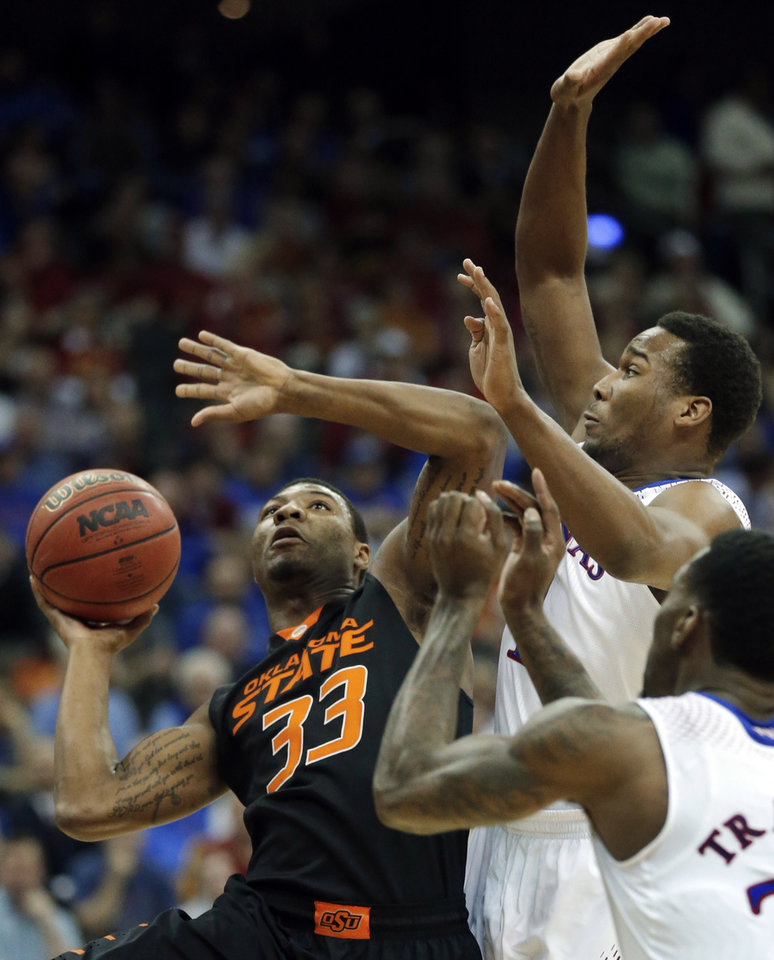 Photo - Oklahoma State guard Marcus Smart (33) shoots while covered by Kansas guard Wayne Selden, Jr. (1) and forward Jamari Traylor, right, during the first half of an NCAA college basketball game in the quarterfinals of the Big 12 Conference men's tournament in Kansas City, Mo., Thursday, March 13, 2014. (AP Photo/Orlin Wagner)