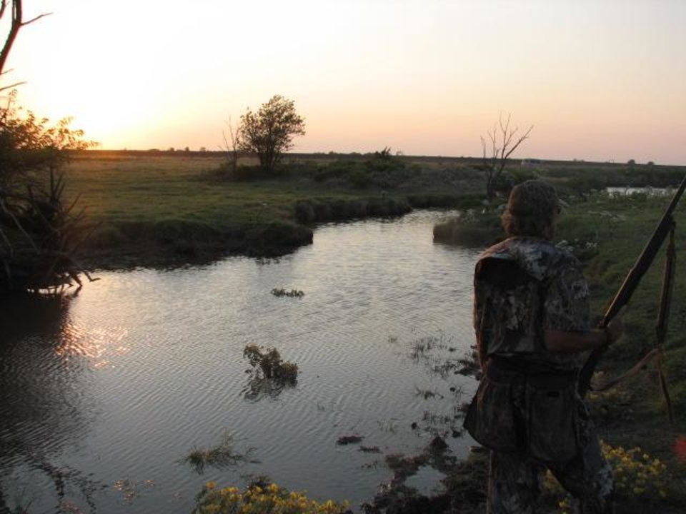 Photo -  A dove hunter in Canadian County waits by a creek at dusk for birds to arrive to the watering hole. Oklahoma's dove season opens Sept. 1. [PHOTO BY ED GODFREY, THE OKLAHOMAN]