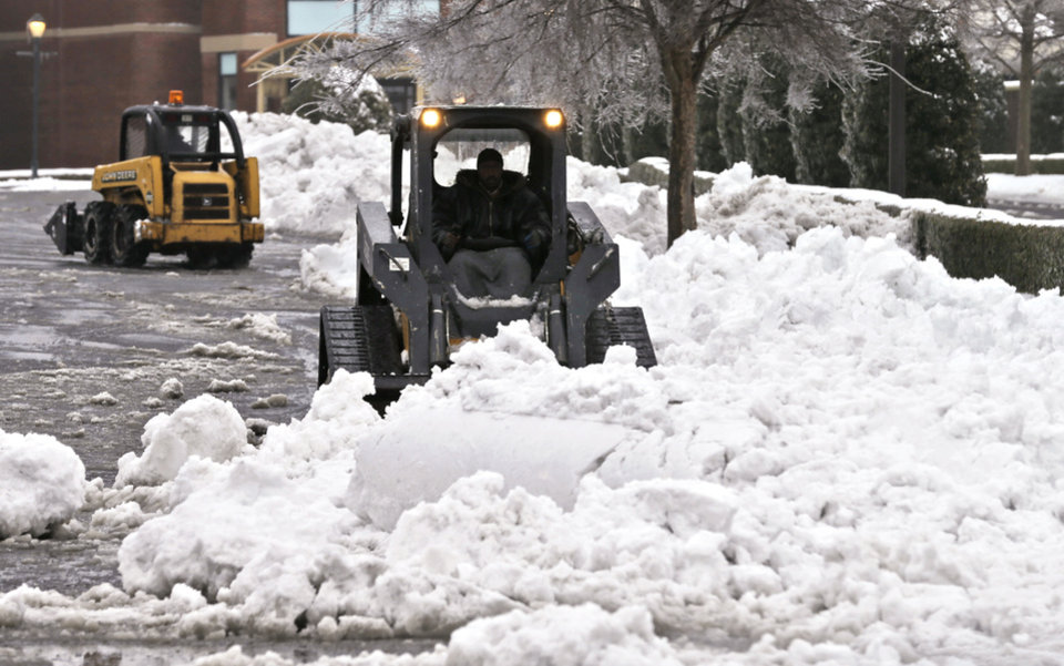 Photo - Crews clear a parking lot at a shopping center in Richmond, Va., Thursday, Feb. 13, 2014. More than a foot of snow in southern and northern Virginia sandwiched the slushy center of the state Thursday, with more rain, snow and sleet threatening to make roads even more treacherous. (AP Photo/Steve Helber)