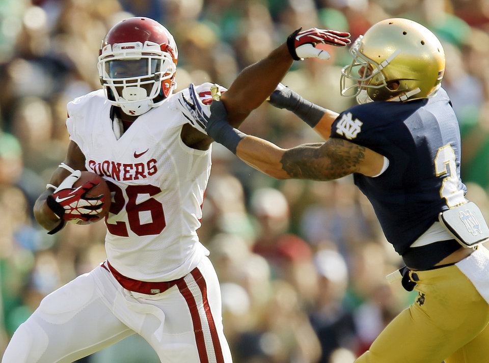 Photo - Oklahoma's Damien Williams (26) tries to get past Notre Dame's Bennett Jackson (2) in the first quarter during a college football game between the University of Oklahoma Sooners (OU) and the Notre Dame Fighting Irish at Notre Dame Stadium in South Bend, Ind., Saturday, Sept. 28, 2013. Photo by Nate Billings, The Oklahoman