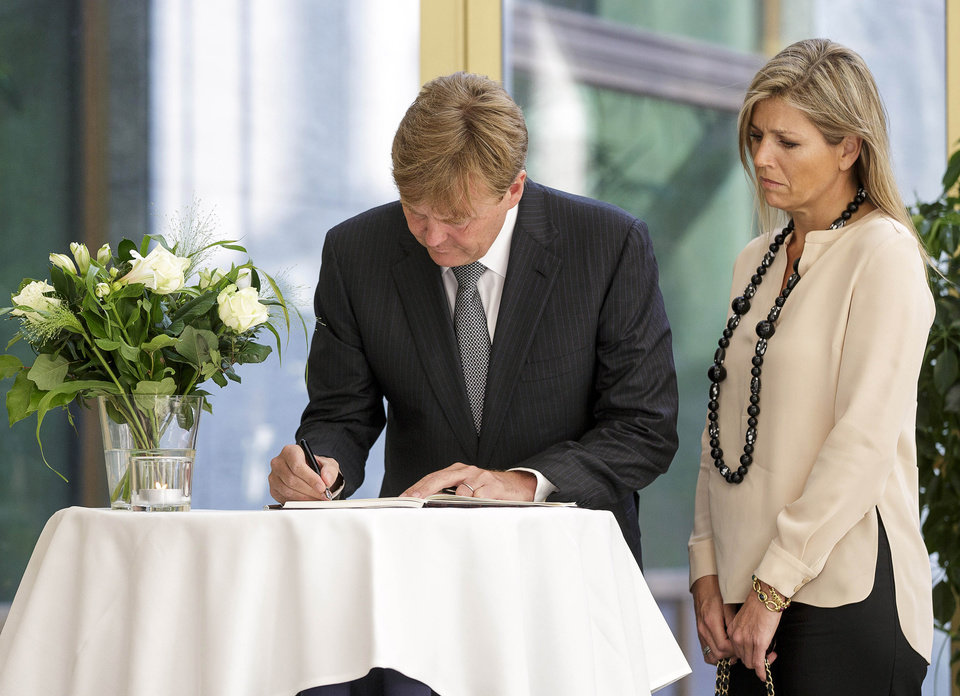 Photo - Dutch King Willem-Alexander, left, signs a condolence register as Queen Maxima looks on at the Ministry of Security and Justice in The Hague, Netherlands, Friday, July 18, 2014. The attack on a Malaysian jetliner Thursday afternoon killed 298 people from nearly a dozen nations, more than half being Dutch, including vacationers, students and a large contingent of scientists heading to an AIDS conference in Australia. (AP Photo/Phil Nijhuis)