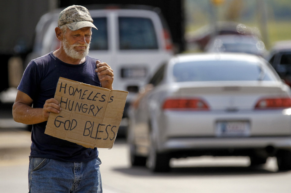 Raymond Hauser, 50, of Joplin, Mo., panhandles Wednesday at Interstate 40 and MacArthur Boulevard  in Oklahoma City. Hauser ended up in Oklahoma after being stranded while hitchhiking to California a month ago. Photo by Chris Landsberger, The Oklahoman