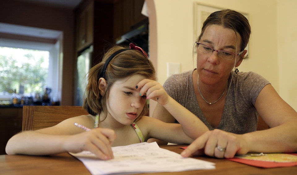 """Photo - Stacey Jacobson-Francis, right, works on math homework with her 6 year old daughter Luci Wednesday, May 14, 2014, at their home in Berkeley, Calif. As schools around the U.S. implement national Common Core learning standards, parents trying to help their kids with math homework say that adding, subtracting, multiplying and dividing has become as complicated as calculus.  Stacey Jacobson-Francis, 41, of Berkeley, California, said her daughter's homework requires her to know four different ways to add. """"That is way too much to ask of a first grader. She can't remember them all, and I don't know them all, so we just do the best that we can,"""" she said. (AP Photo)"""