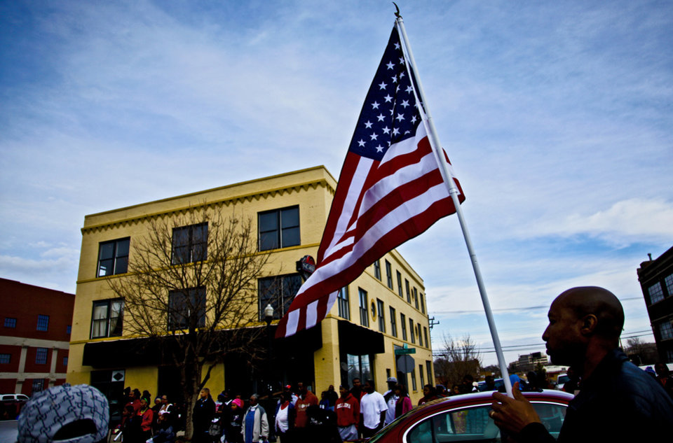Photo - A parade spectator carries an American Flag as he watches the parade during the Martin Luther King Jr. parade in downtown on Monday, Jan. 17, 2011, in Oklahoma City, Okla. .  