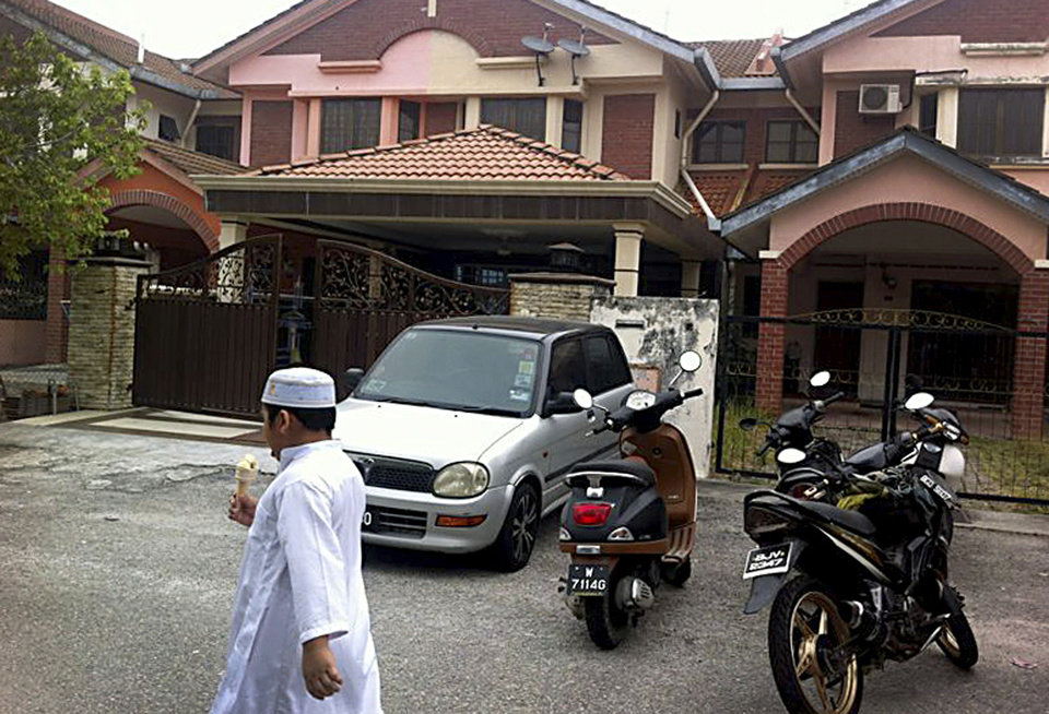 Photo - A Muslim boy leaves a mosque after Friday prayers, just down the road from the home of Fariq Abdul Hamid, co-pilot of the missing Malaysia Airlines jetliner MH370, center, Friday, March 14, 2014 in Shah Alam, Malaysia. The pilots of the missing Malaysia Airlines passenger jet were a contented middle-aged family man passionate enough about flying to build his own simulator and a 27-year-old contemplating marriage who had just graduated to the cockpit of the Boeing 777. Details about the men have emerged from interviews with neighbors, Malaysia Airlines staff, a religious leader and from social networks and news reports in Malaysia and Australia.(AP Photo/Eileen Ng)