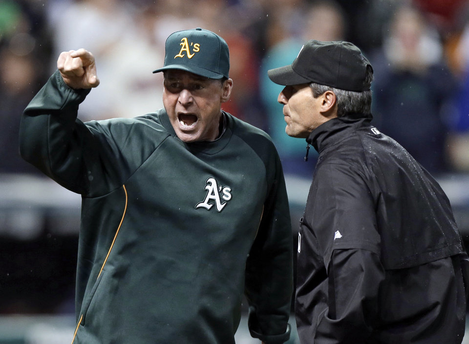 Photo - Oakland Athletics manager Bob Melvin, left, argues with umpire Angel Hernandez after a review failed to turn a double by Adam Rosales into a home run in the ninth inning of the A's baseball game against the Cleveland Indians on Wednesday, May 8, 2013, in Cleveland. Melvin was ejected. The Indians won 4-3. (AP Photo/Mark Duncan)