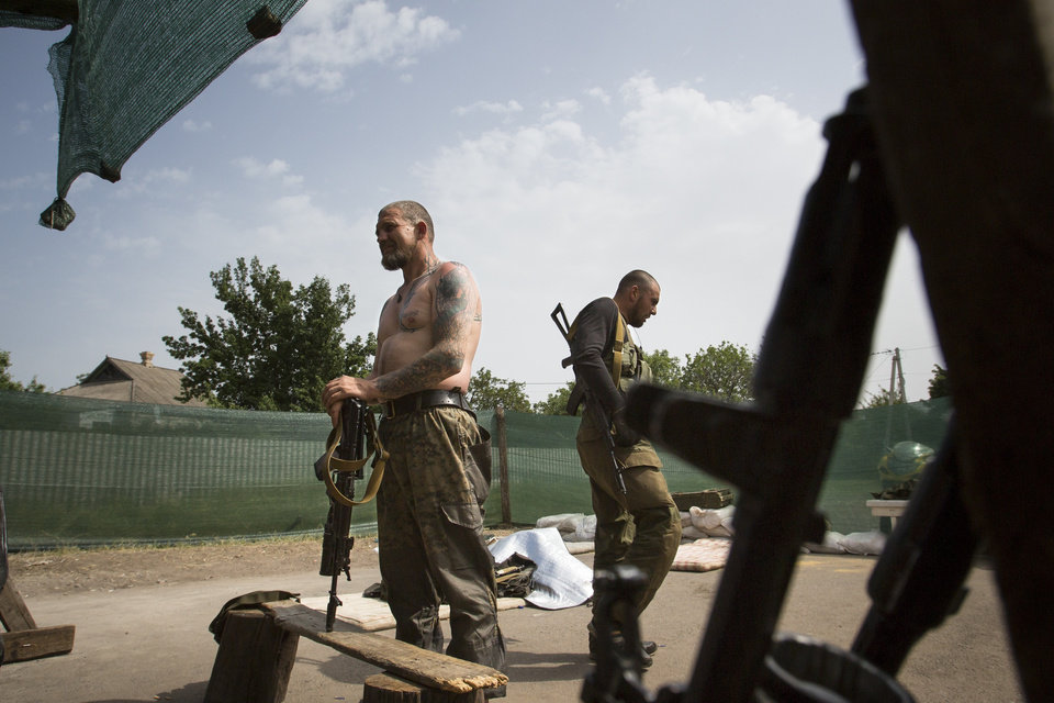 Photo - Pro-Russians rest at a checkpoint outside Slovyansk, eastern Ukraine, Monday, May 19, 2014.  Heavy mortar fire outside the eastern Ukrainian city of Slovyansk has damaged a large gas pipeline and set off a fire. Slovyansk has been the epicenter of fighting between Ukrainian troops and pro-Russian insurgents, who have seized government buildings across the east.  (AP Photo/Alexander Zemlianichenko)