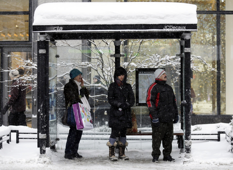 Photo - People wait for a bus at a bus stop in downtown Chicago on Sunday, Jan. 5, 2014. Sunday night temperatures will drastically drop to about minus 20 degrees. (AP Photo/Nam Y. Huh)