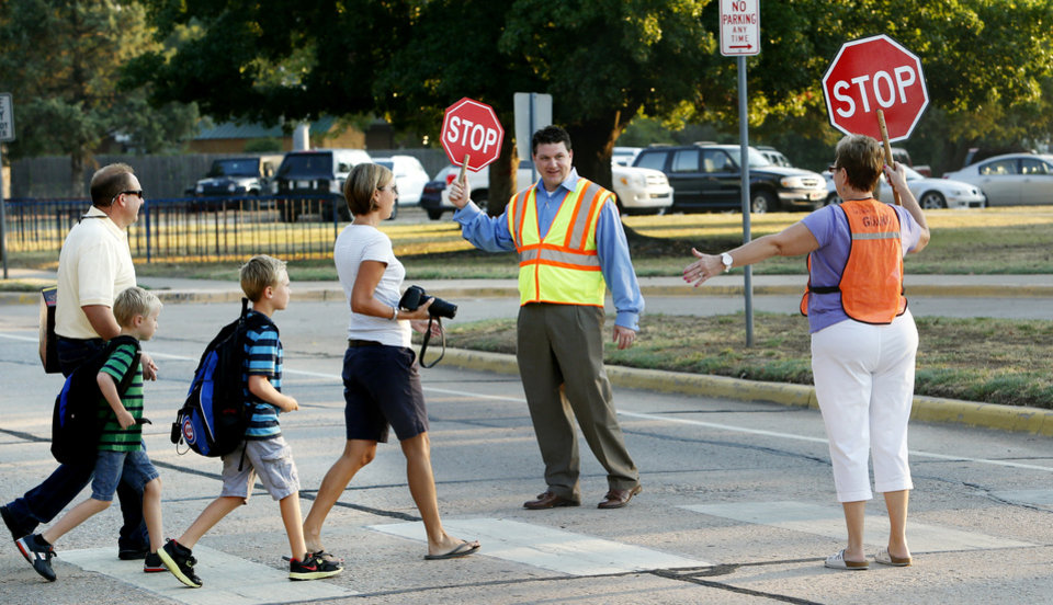 Crossing guards Bo Jett and Linda McCarthy stop traffic as students arrive for the first day of school at Monroe Elementary School on Wednesday, Aug. 22, 2012 in Norman, Okla.  Photo by Steve Sisney, The Oklahoman