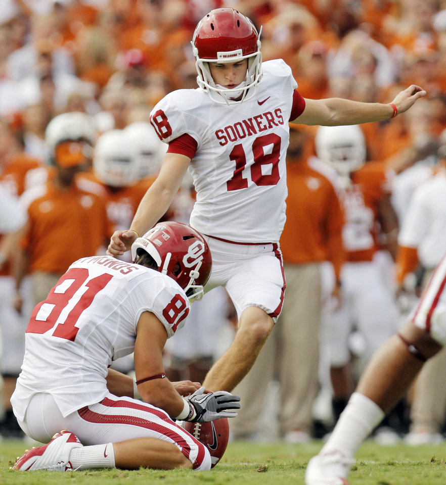Photo - OU's Michael Hunnicutt kicks a field goal as Nyko Symonds (81) holds in the first half during the Red River Rivalry college football game between the University of Oklahoma Sooners (OU) and the University of Texas Longhorns (UT) at the Cotton Bowl in Dallas, Friday, Oct. 7, 2011. Photo by Nate Billings, The Oklahoman