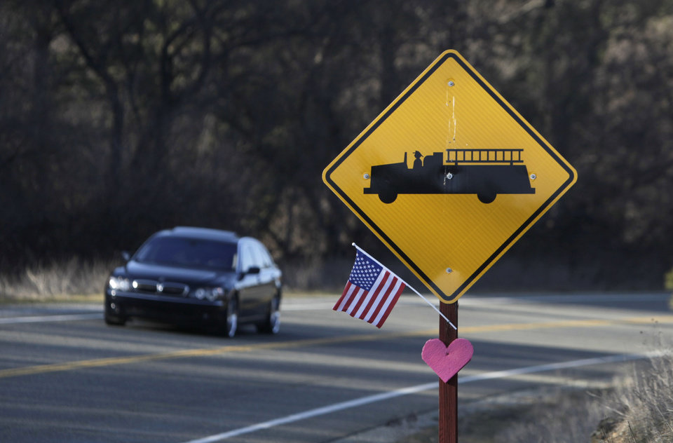 Photo - In this photo taken Wednesday, Feb. 13, 2013, a flag and heart adorn a fire station warning sign near Greenwood, Calif.  While rural residents depend on firefighters to defend their property when fires threaten, many oppose a fire prevention fee.(AP Photo/Rich Pedroncelli)