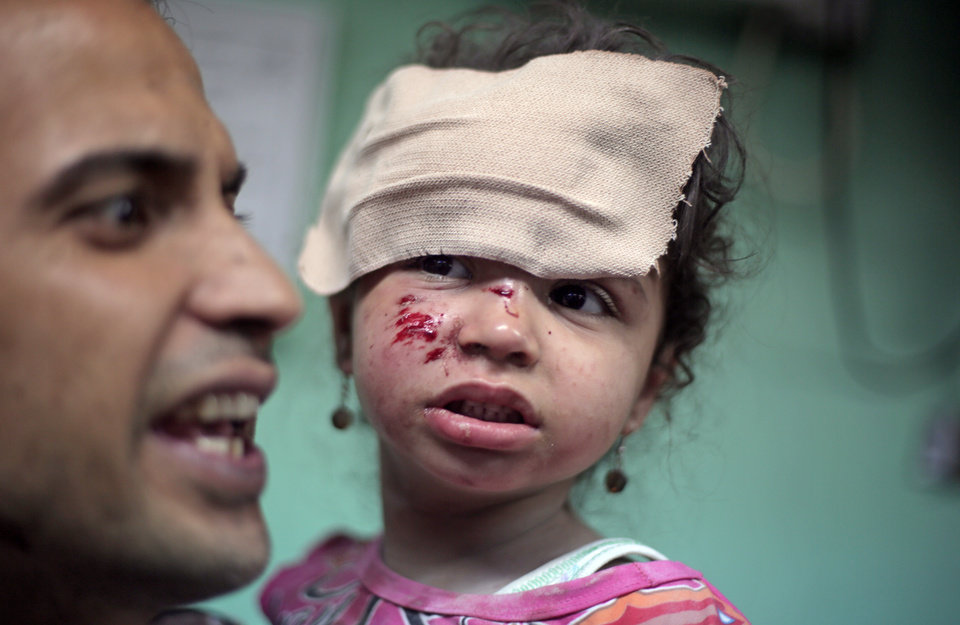 Photo - A Palestinian man carries a wounded girl at the Kamal Adwan hospital in Beit Lahiya after receiving treatment for her wounds caused by an Israeli strike at a U.N. school in Jebaliya refugee camp, northern Gaza Strip, Wednesday, July 30, 2014. Several Israeli tank shells slammed into the crowded U.N. school used as shelter for refugees in the Gaza war early on Wednesday. (AP Photo/Khalil Hamra)