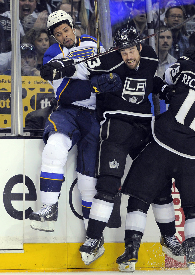 Photo -   St. Louis Blues right wing Ryan Reaves, left, and Los Angeles Kings defenseman Willie Mitchell collide during the third period in Game 4 of an NHL hockey Stanley Cup second-round playoff series, Sunday, May 6, 2012, in Los Angeles. The Kings won 3-1 and won the series 4-0. (AP Photo/Mark J. Terrill)