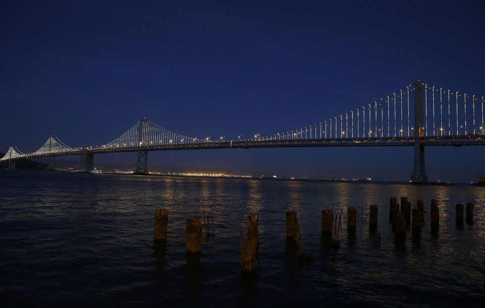 In this Wednesday, Feb. 20, 2013,  photo,lights are turned on along the western half of the San Francisco-Oakland Bay Bridge on Pier 14 in San Francisco. The San Francisco-Oakland Bay Bridge has been turned into the latest, and by far the biggest, backdrop for New York artist Leo Villareal, who has individually programmed 25,000 white lights spaced a foot apart on 300 of the span�s vertical cables to create what is being billed as the world�s largest illuminated sculpture. (AP Photo/Jeff Chiu)