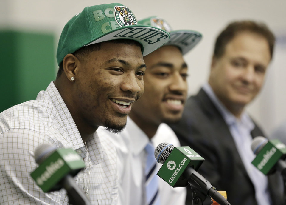 Boston Celtics 2014 NBA basketball draft picks Marcus Smart, left, and James Young, center, face reporters as Celtics co-owner Stephen Pagliuca, right, looks on during a news conference held to introduce the players, Monday, June 30, 2014, in Waltham, Mass. (AP Photo/Steven Senne)