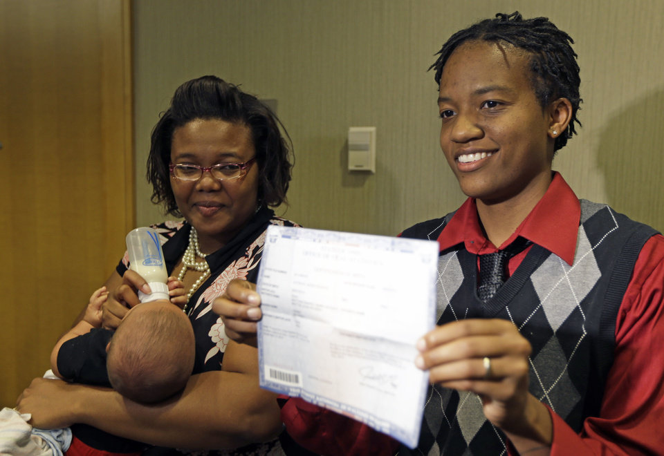 Photo - Kelly Noe, right, stands with her partner Kelly McCracken, as Noe holds a birth certificate for their daughter that has both of their names on it, Wednesday, Aug. 6, 2014, in Cincinnati. The couple are plaintiffs in the Ohio gay marriage case heard Wednesday in Cincinnati. A three judge panel of the 6th U.S. Circuit Court of Appeals heard arguments in six gay marriage fights from four states, Kentucky, Michigan, Ohio and Tennessee. (AP Photo/Al Behrman)