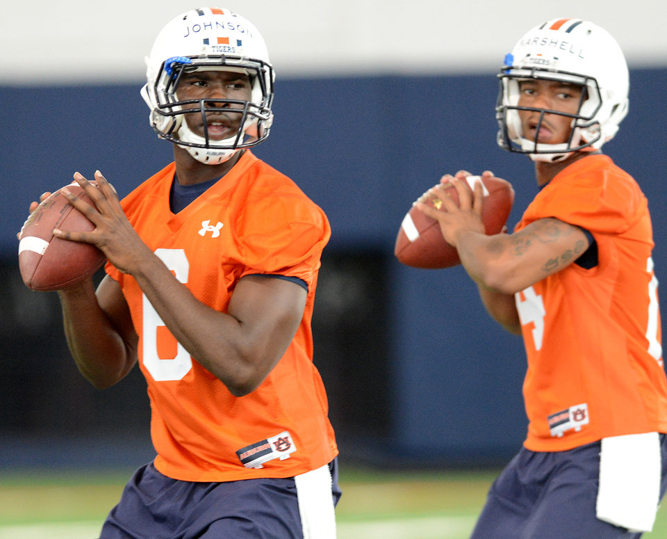 Photo - FILE - In this Aug. 2, 2013, file photo, Auburn quarterbacks Jeremy Johnson (6) and Nick Marshall (14) warm up during the first day of NCAA college football practice in Auburn, Ala.  Johnson says he has no idea if he's starting against Arkansas with starter Nick Marshall being held out for at least the opening. He does have one prediction: Marshall will win the Heisman Trophy. (AP Photo/AL.com, Julie Bennett, File) MAGS OUT
