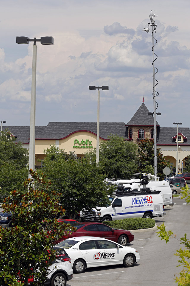 Photo - Satellite trucks line the parking lot where the highest Powerball jackpot worth an estimated $590.5 million was sold, at a Publix supermarket in Zephyrhills, Fla. on Sunday, May 19, 2013. (AP Photo/Scott Iskowitz)