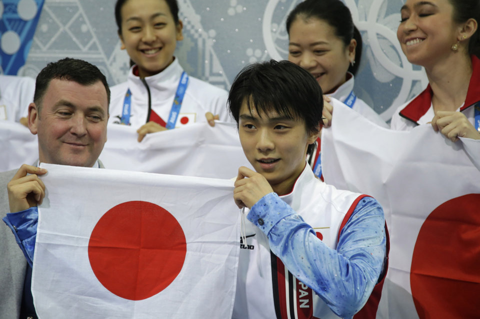 Photo - Yuzuru Hanyu of Japan holds up the national flag after competing in the men's team short program figure skating competition at the Iceberg Skating Palace during the 2014 Winter Olympics, Thursday, Feb. 6, 2014, in Sochi, Russia. (AP Photo/Darron Cummings, Pool)
