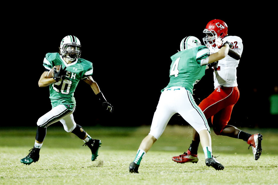 Photo - McGuinness' jack Merrill blocks Titan Nate Christmon allowing a long punt return by Braden Roy in the first half as the Carl Albert Titans play the Bishop McGuinness Irish on Friday, Oct. 4, 2013 in Oklahoma City, Okla.  Photo by Steve Sisney, The Oklahoman