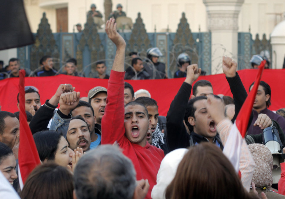 Egyptian protesters shout slogans against President Mohammed Morsi  in front of the presidential palace in Cairo, Egypt, Friday, Jan.25, 2013. Two years after Egypt's revolution began, the country's schism was on display Friday as the mainly liberal and secular opposition held rallies saying the goals of the pro-democracy uprising have not been met and denouncing Islamist President Mohammed Morsi. (AP Photo/Amr Nabil) ORG XMIT: AMR120