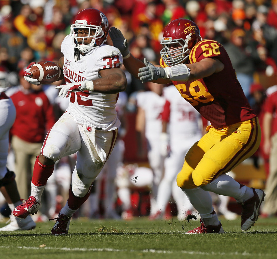Photo - Oklahoma's Samaje Perine (32) attempts to break away from Iowa State's Cory Morrissey (58) on a carry in the second quarter during a college football game between the University of Oklahoma Sooners (OU) and the Iowa State Cyclones (ISU) at Jack Trice Stadium in Ames, Iowa, Saturday, Nov. 1, 2014. Photo by Nate Billings, The Oklahoman