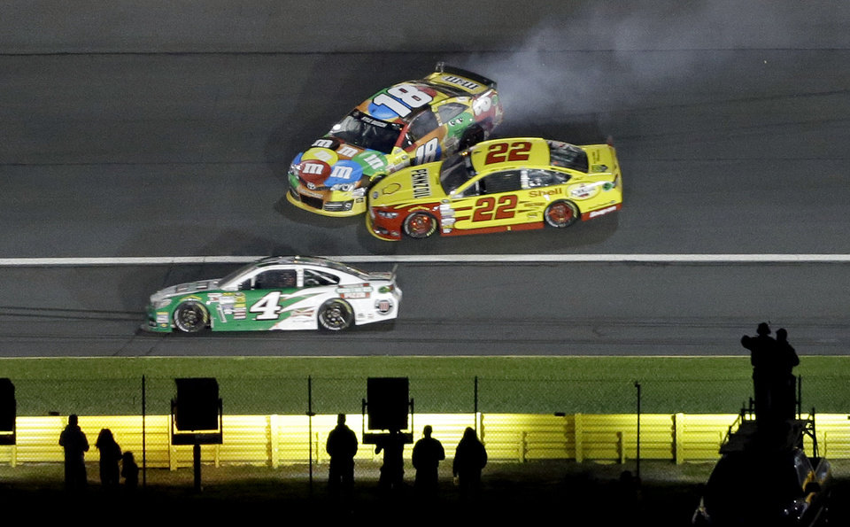 Photo - Kyle Busch (18) and Joey Logano (22) collide in Turn 3 as Kevin Harvick (4) drives low during the NASCAR Sprint All-Star auto race at Charlotte Motor Speedway in Concord, N.C., Saturday, May 17, 2014. (AP Photo/Gerry Broome)