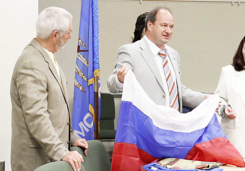 Photo - Sergey Gorevskiy, mayor of Engels, in Russia, gives a regional flag to Edmond Mayor Charles Lamb after signing a proclamation designating a Sister Cities  partnership. PHOTO BY PAUL HELLSTERN, THE OKLAHOMAN.