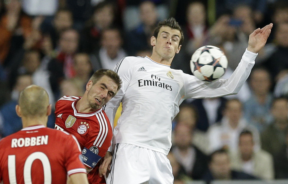 Photo - Bayern's Philipp Lahm and Real's Gareth Bale, right, go for a header as Bayern's Arjen Robben, left, looks on during a  Champions League semifinal first leg soccer match between Real Madrid and Bayern Munich at the Santiago Bernabeu stadium in Madrid, Spain, Wednesday, April 23, 2014. (AP Photo/Paul White)