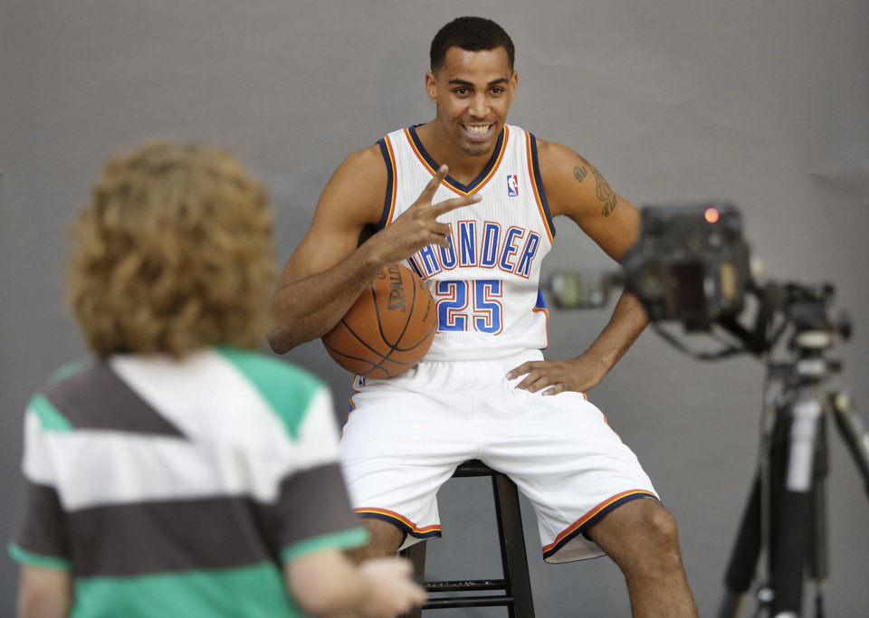 Tabius Landsberger, 11, takes a photo of Thabo Sefolosha during media day with the Oklahoma City Thunder in Oklahoma City, Thursday September  27, 2013. Photo By Steve Gooch, The Oklahoman