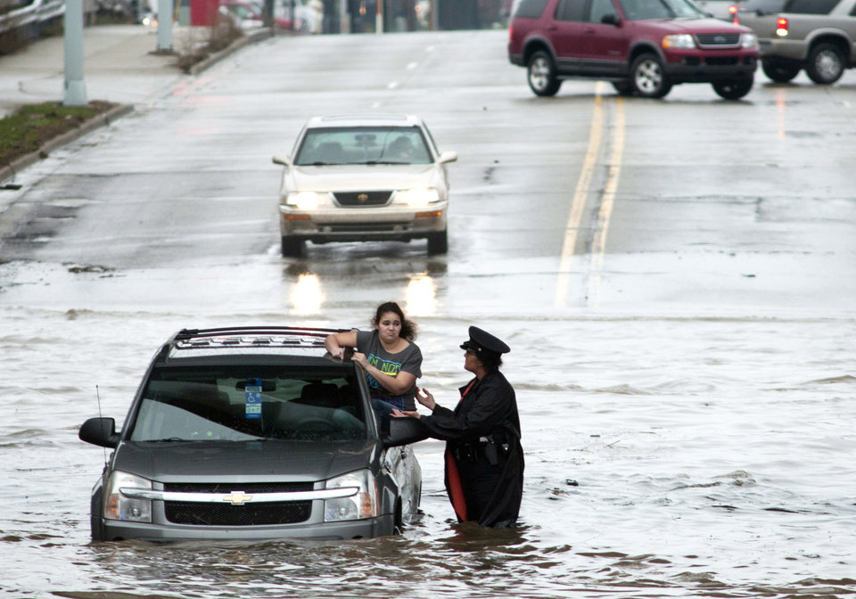 Photo - Police officer Shannon Vandenheuvel helps Barbara Jones from her partially submerged car   in Grand Rapids, Mich. Thursday, April 18, 2013. Middle America was getting everything nature has to throw at it on Thursday, from snow in the north to tornadoes in the Plains, and with torrential rains causing floods and transportation chaos in several states. (AP Photo/Grand Rapids Press, Chris Clark)