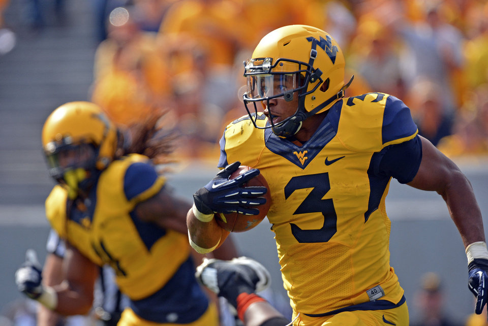 Photo - West Virginia running back Charles Sims (3) rushes for 25 yards in the third quarter of an NCAA college football game against Oklahoma State in Morgantown, W.Va., on Saturday, Sept. 28, 2013. (AP Photo/Tyler Evert) ORG XMIT: WVTE110