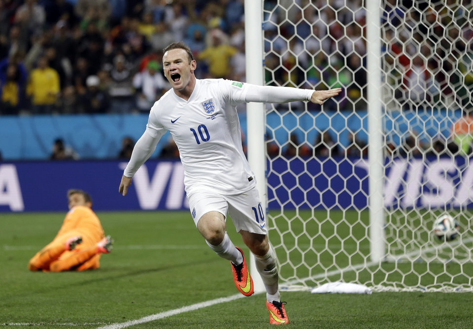 Photo - Uruguay's goalkeeper Fernando Muslera looks back as England's Wayne Rooney celebrates after scoring his side's first goal during the group D World Cup soccer match between Uruguay and England at the Itaquerao Stadium in Sao Paulo, Brazil, Thursday, June 19, 2014.  (AP Photo/Kirsty Wigglesworth)