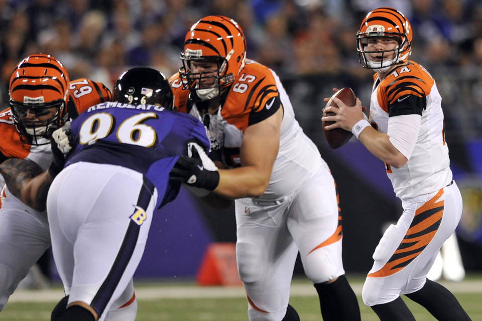 Photo -   Cincinnati Bengals quarterback Andy Dalton 914) looks for a receiver as center Jeff Faine (62) and guard Clint Boling (65) hold back Baltimore Ravens nose tackle Maake Kemoeatu in the first half of an NFL football game in Baltimore, Monday, Sept. 10, 2012. (AP Photo/Gail Burton)