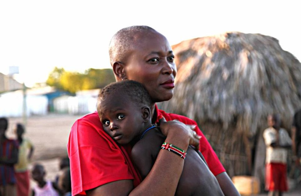 Photo - Maisha Project Executive Director Beatrice Williamson comforts a child in Kenya. [PHOTO PROVIDED]