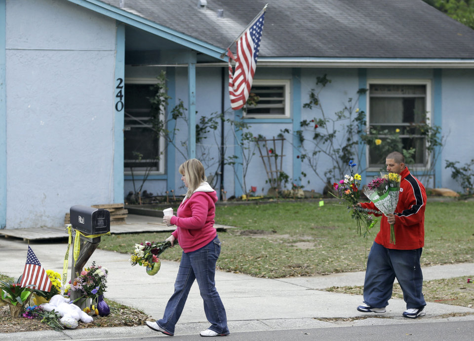 Jeremy Bush, right, carries flowers to a makeshift memorial Sunday, March 3, 2013, outside a home where a sinkhole opened up underneath a bedroom late Thursday evening and swallowed Jeremy's brother Jeffrey in Seffner, Fla. The home is is set to be demolished Sunday. (AP Photo/Chris O'Meara)