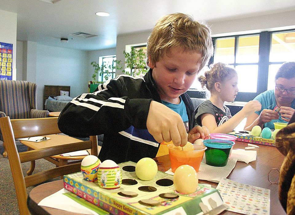 Tyler Thomas places Easter eggs in a carton to dry while Twyla Bell colors eggs with physical therapy student Katy Paxton during a recent cooking class at the J.D. McCarty Center in Norman. PHOTO PROVIDED