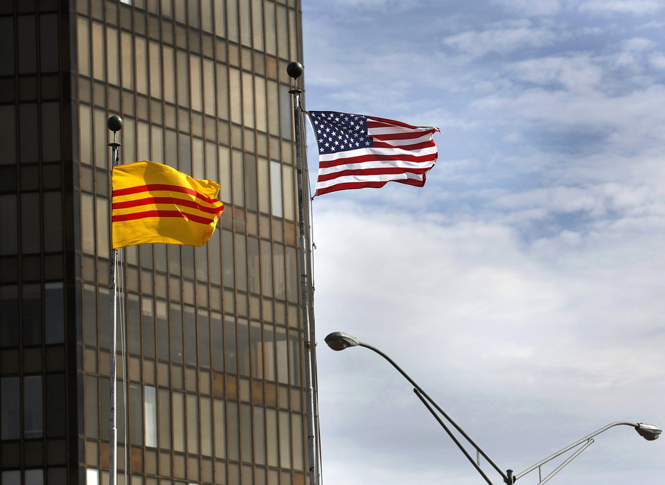 Photo -  An American flag flies alongside the flag of Vietnam before it was occupied by a Communist regime, in front of the building on Classen Blvd. where Mai Ly Do has operated a Vietnamese radio station for 12 years. Mai helps keep the Vietnamese community connected, using their native language. During the May 20 storms, Mai stayed at her radio studio and kept broadcasting to ensure that Vietnamese Oklahomans knew when to take shelter. She provides an important service for a dedicated group of listeners.    Jim Beckel -  THE OKLAHOMAN
