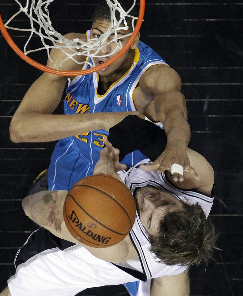 Photo - New Orleans Hornets' Anthony Davis (23) defends San Antonio Spurs' Tiago Splitter (22), of Brazil, during the first quarter of an NBA basketball game, Wednesday, Jan. 23, 2013, in San Antonio. (AP Photo/Eric Gay)