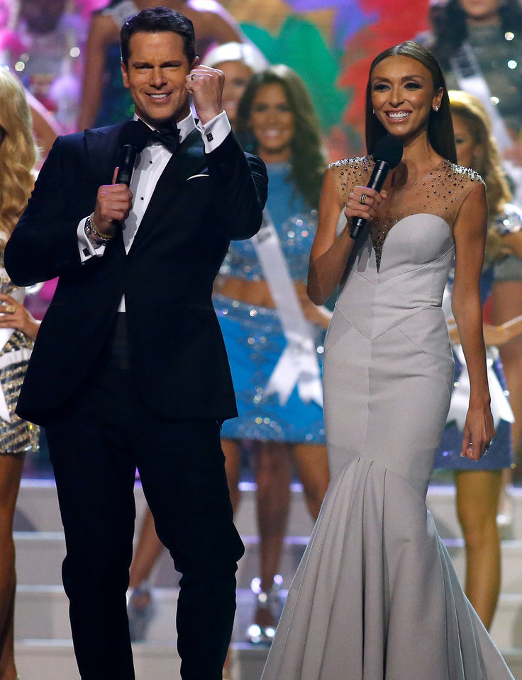 Photo - Hosts Thomas Roberts, left, and Giuliana Rancic welcome contestants to the stage during the Miss USA 2014 pageant in Baton Rouge, La., Sunday, June 8, 2014. (AP Photo/Jonathan Bachman)