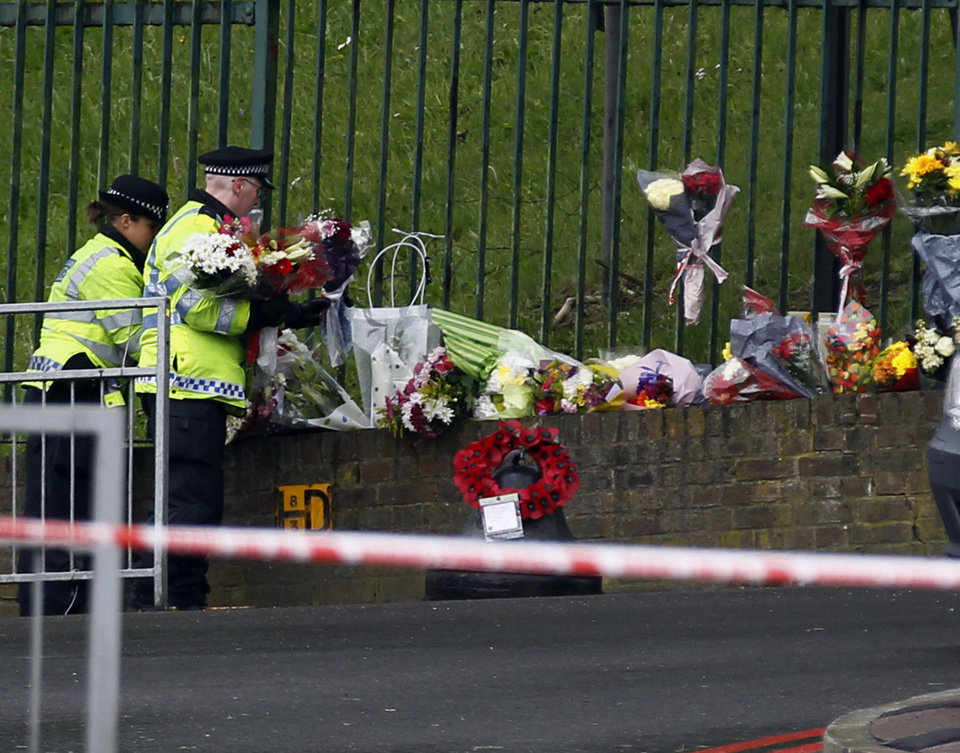 Photo - Police officers lay down floral tributes handed to them by members of the public at the scene of a terror attack in Woolwich, southeast London, Thursday, May 23, 2013.  The British government's emergency committee met Thursday after two attackers killed a man in a daylight attack in London that raised fears terrorism had returned to the capital. (AP Photo/Sang Tan)